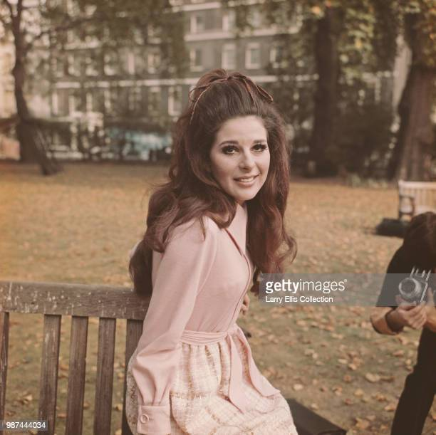 American singer and songwriter Bobbie Gentry posed sitting on a park bench in a London square on 13th October 1969