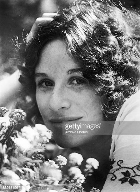 American singer and songwriter Carole King posing with flowers circa 1975