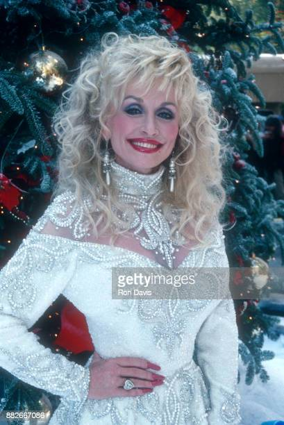 American singer and songwriter Dolly Parton poses for a portrait in front of a Christmas Tree circa December 1988 in Lake Tahoe California