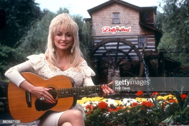 American singer and songwriter Dolly Parton poses for a portrait with her guitar at Dollywood circa 1993 in Pigeon Forge Tennessee