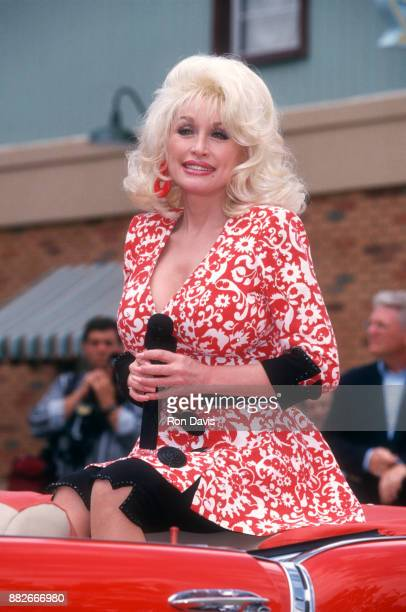 American singer and songwriter Dolly Parton rides in the back of a convertible during the 10th Anniversary of her Dollywood theme park circa April...