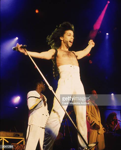 American singer and songwriter Prince stands on stage with his arms outstretched wearing highwaisted white pants circa 1990