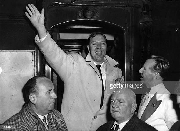 American singer Bill Haley of the rock 'n' roll band Bill Haley And His Comets waving to fans on his arrival at Waterloo station
