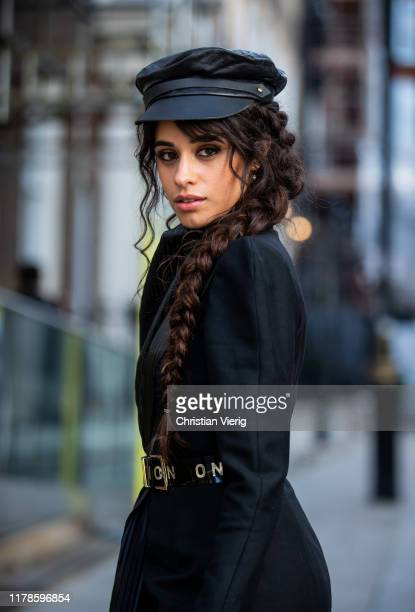 American singer Camila Cabello is seen wearing black belted dress Ronald van der Kemp flat cap on October 02 2019 in London England