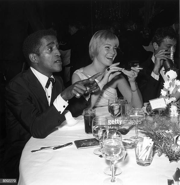 American singer dancer and actor Sammy Davis Jr sits at a table with his wife May Britt during a Thalian Party Hollywood California A glass filled...
