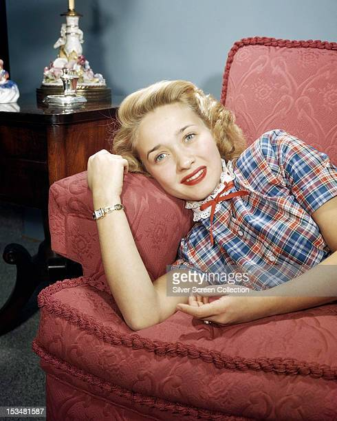 American singer dancer and actress Jane Powell lying on a red sofa circa 1955