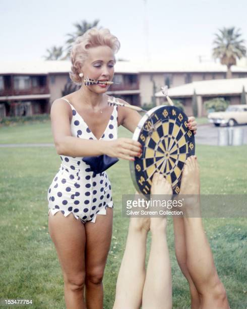 American singer dancer and actress Jane Powell playing darts in a black and white polkadot onepiece swimsuit circa 1955 Her dartboard is being held...