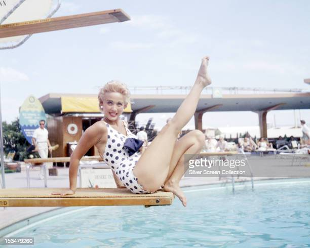 American singer dancer and actress Jane Powell sitting on a diving board in a black and white polkadot onepiece swimsuit circa 1955 circa 1955