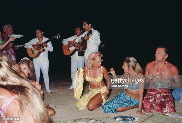 American singer Dinah Shore and actor Kirk Douglas at a beach party in Acapulco Mexico January 1968