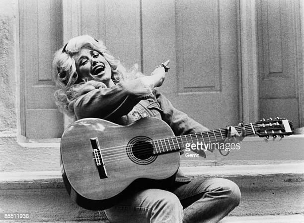 American singer Dolly Parton singing with a guitar, circa 1970.