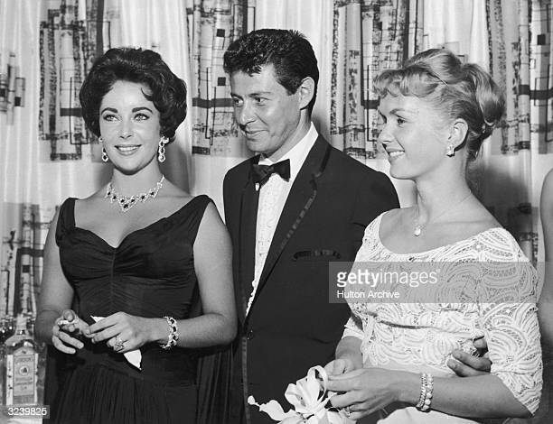 American singer Eddie Fisher, wearing a tuxedo, stands with arm around his wife, American actor Debbie Reynolds and smiles while looking at...