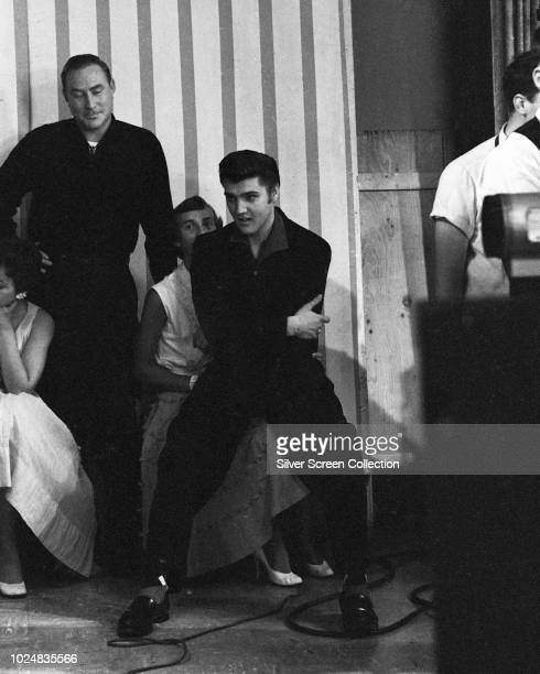 American singer Elvis Presley sitting with disc jockey Dewey Phillips during his appearance on Wink Martindale's television show 'Teenage Dance...
