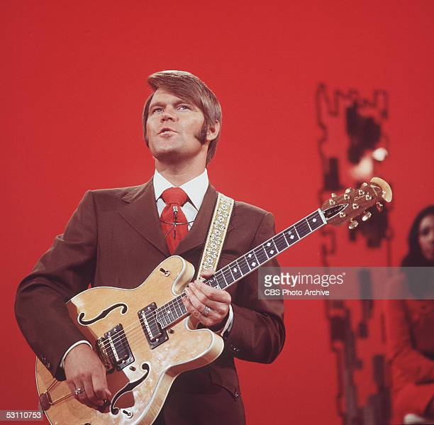 American singer, guitarist, and television host Glen Campbell adjusts a dial on his Ovation Deluxe acoustic - electric guitar in a still from his CBS...