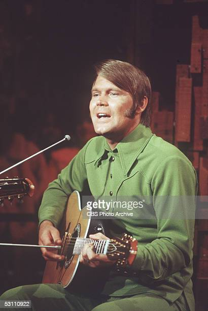 American singer, guitarist, and television host Glen Campbell sings into a microphone and strums his acoustic - electric guitar in a still from his...
