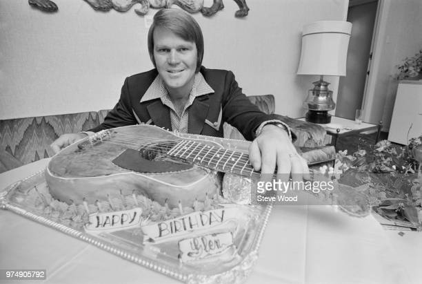 American singer, guitarist, songwriter, television host, and actor Glen Campbell with his guitar-shaped birthday cake, UK, 25th April 1973.