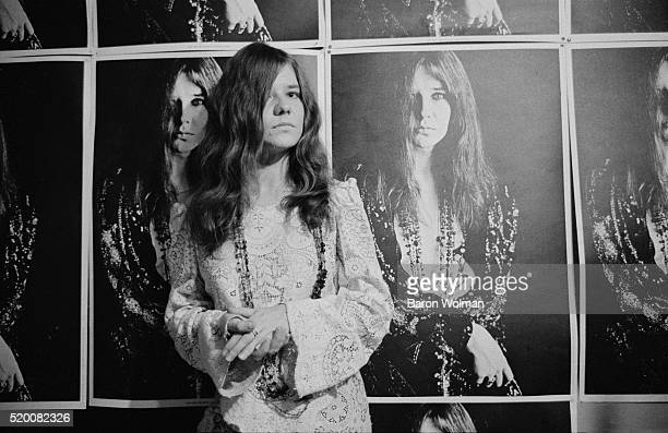 American singer Janis Joplin poses at her home in front of a Bob Seidemann poster in HaightAshbury San Francisco November 1967