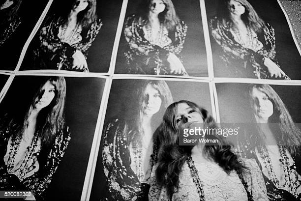 American singer Janis Joplin poses at her home in front of a Bob Seidemann poster in HaightAshbury San Francisco November 1967