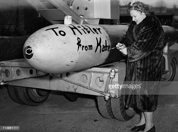 American singer Kate Smith paints the message 'To Hitler from Kate' on the side of a torpedo at a US Navy submarine base in New London Connecticut...