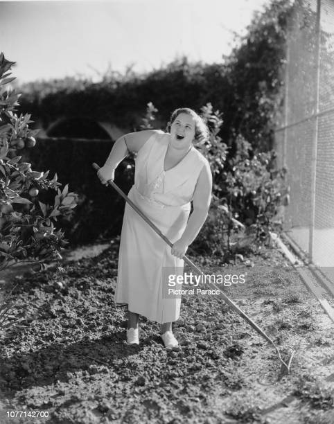 American singer Kate Smith sings while working in the garden circa 1935