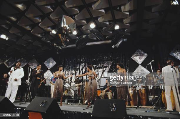 American singer Luther Vandross pictured wearing a white suit on far left as he performs with Herbie Mann at the 1977 Montreux Jazz Festival in the...