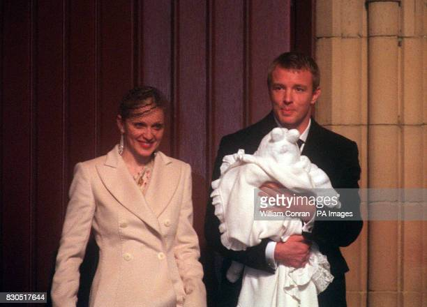 American singer Madonna and British film director Guy Ritchie with their fourmonthold baby son Rocco wrapped in a white christening gown after the...