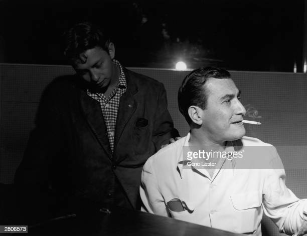 American singer Mel Torme rests his hand on the shoulder of jazz musician and bandleader Artie Shaw during a recording session for the Musicraft...