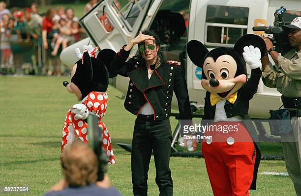American singer Michael Jackson poses with Mickey Mouse and Minnie Mouse whilst in London for a concert at Wembley 30th July 1992