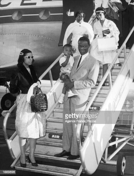 American singer Nat King Cole descends the stairs to an airplane holding his son Kelly accompanied by his wife Maria Ellington their daughter Carol...