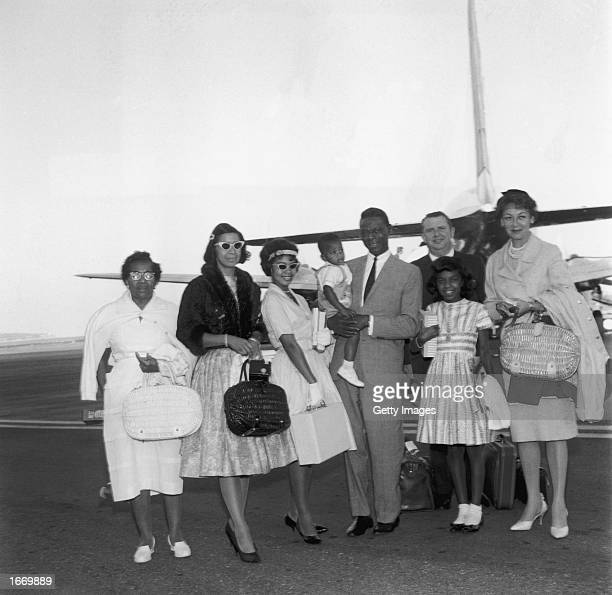 American singer Nat King Cole poses with his family and friends in front of an airplane on the tarmac at Nice Airport France August 5 1960 Nat holds...