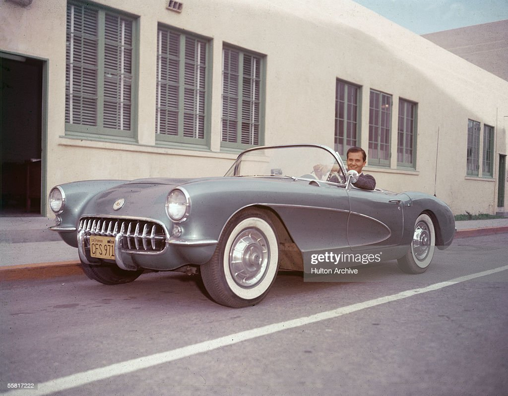 American singer Pat Boone sits in his 1956 or 1957 Chevrolet Corvette sports car and smiles, late 1950s.
