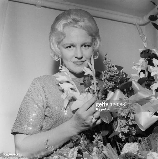 American singer Peggy Lee posed with a bouquet of flowers backstage prior to performing at the Pigalle Club in London in July 1961