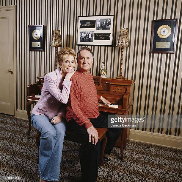 American singer pianist and composer Neil Sedaka at home with his wife Leba New York City 2009 A photograph behind the piano shows Sedaka's 1958...