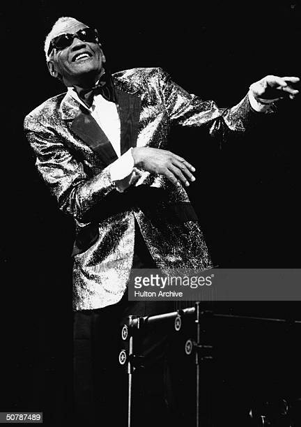 American singer pianist and songwriter Ray Charles stands and gestures while performing in concert 1980s