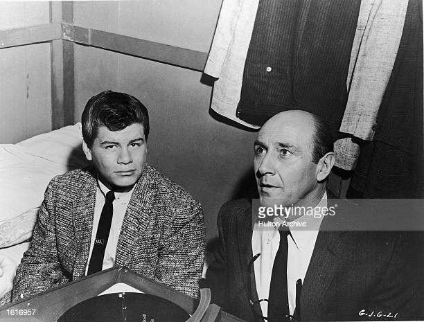 American singer Ritchie Valens sits with actor Milton Frome near a record player in a dressing room on the set of the film 'Go Johnny Go' directed by...