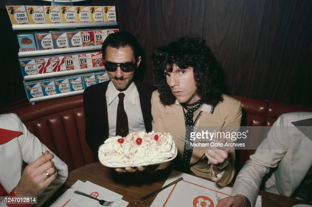 American singer Russell Mael with his brother Ron Mael, eating a cream dessert, circa 1975. Together they formed the band Sparks.