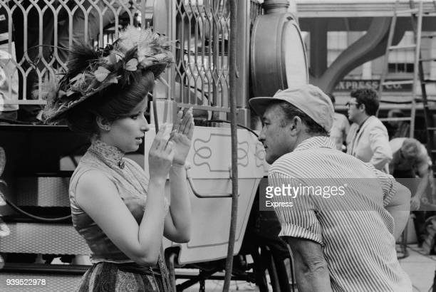 American singer songwriter and actress Barbara Streisand with director Gene Kelly on the set of romantic comedy musical film 'Hello Dolly' US 19th...
