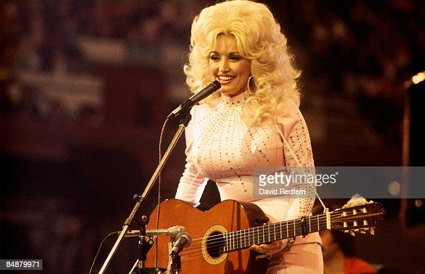 American singer, songwriter and actress Dolly Parton, performs with a guitar, 1976.