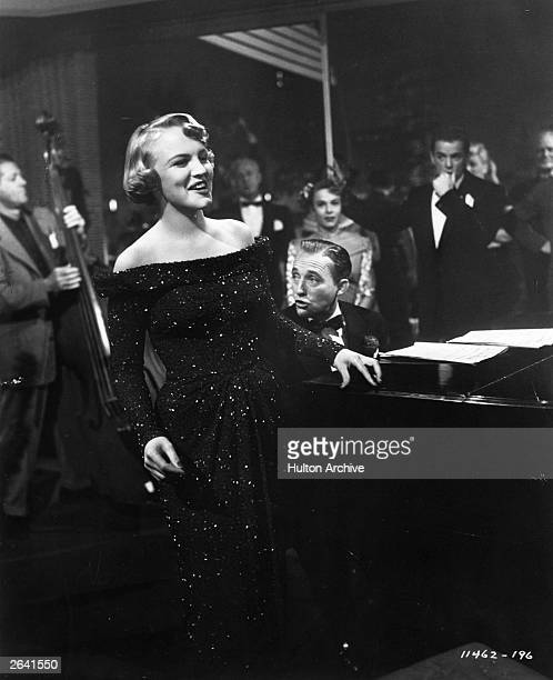 American singer songwriter and actress Peggy Lee performing in a scene from the film 'Mr Music' accompanied on the piano by Bing Crosby The film was...
