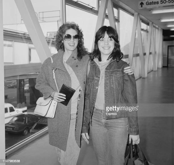American singer, songwriter and musician Emmylou Harris with her daughter Mika Hallie Slocum at Heathrow Airport, London, UK, 15th April 1984.