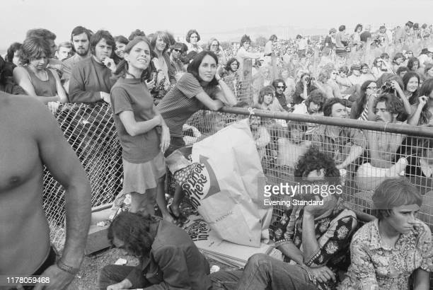 American singer songwriter and musician Joan Baez joins rock fans in the audience to watch a band perform on stage at the Isle of Wight Festival 1970...