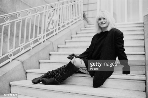 American singer songwriter model and actress Debbie Harry sitting on a staircase UK 21st November 1983