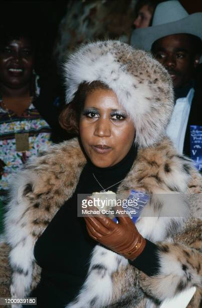 American singer, songwriter, pianist, and civil rights activist Aretha Franklin , wearing fur coat and hat, eats an apple while in attendance at the...