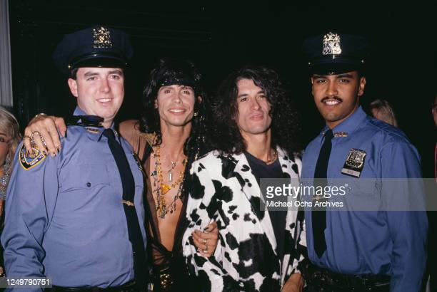 American singer Steven Tyler and American guitarist Joe Perry, both of rock band Aerosmith, posing between two NYPD officers at the 2nd International...