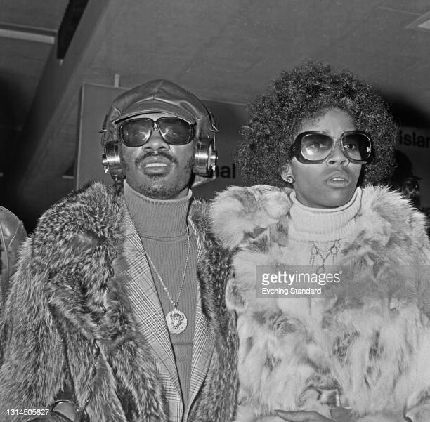 American singer Stevie Wonder arrives at Heathrow Airport in London with singer and songwriter Yvonne Wright, UK, 24th January 1974. Wonder is in the...