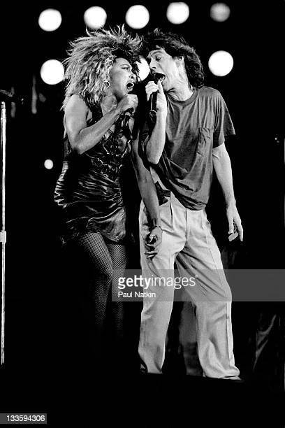 American singer Tina Turner performs with British musician Mick Jagger of the band The Rolling Stones on stage at John F Kennedy Stadium for the Live...