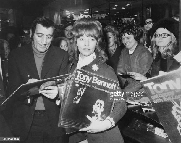 American singer Tony Bennett autographs a copy of his LP 'Get Happy with the London Philharmonic Orchestra' for a fan at Chappells Music Centre in...