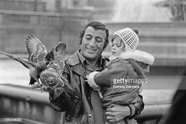 American singer Tony Bennett feeding the pigeons with his daughter Joanna, UK, 14th January 1972.