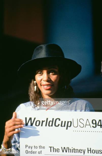 American singer Whitney Houston with a giant cheque made out to her charity with the words 'World Cup USA 94' 1994