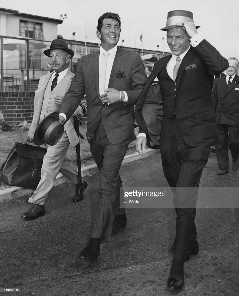 American singers and actors Dean Martin (1917 - 1995) (centre) and Frank Sinatra (right) arriving at London airport, their friend and famed Beverly Hills restauranteur Mike Romanoff is with them.