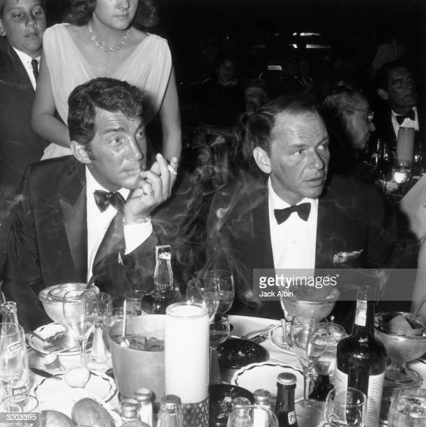American singers and actors Dean Martin and Frank Sinatra attend the opening night performance of American singer Eddie Fisher at the Cocoanut Grove...